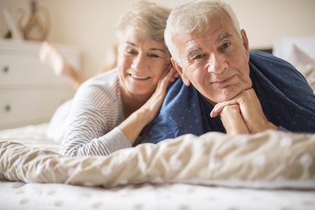 amantes en la cama: par mayor feliz que se acuesta en la cama