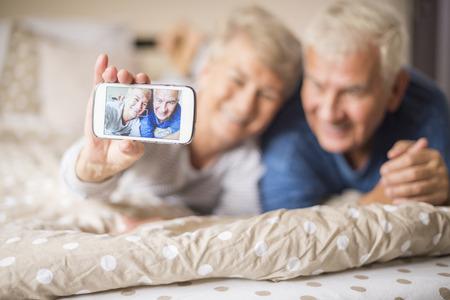enamorados en la cama: Selfie tomada por una pareja de ancianos alegre Foto de archivo