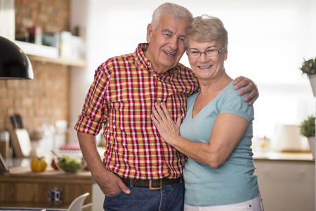 looking at camera: Cheerful senior marriage in the domestic kitchen