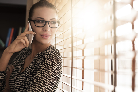 turn away: Woman talking on the phone next to the window Stock Photo