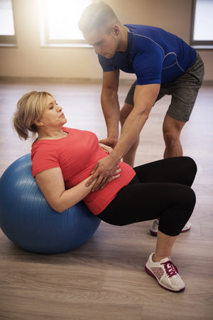 obese man: Coach assisting with exercises of mature woman Stock Photo