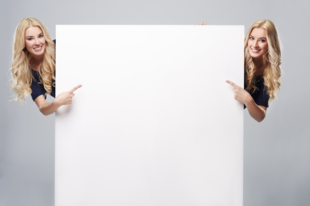 a placard: Adult girls pointing at blank placard