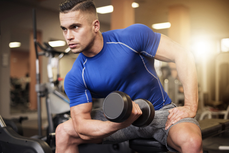 Man focused on shoulder workout Stock Photo