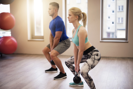 Couple focused on workout with kettles