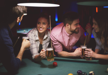 pool game: Two couples playing pool game