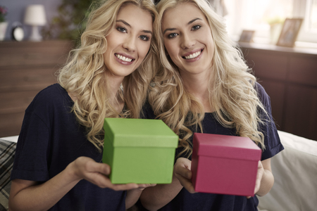 twin sister: They have little boxes with presents Stock Photo