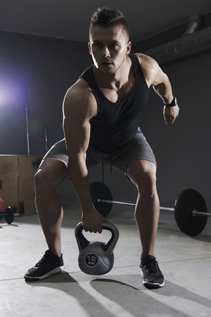 Man lifting kettlebell with one hand