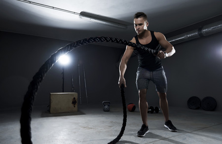 Athletic man efforting on crossfit training with ropes Imagens - 55279285