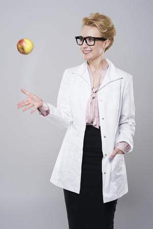 tossing: Female doctor tossing an apple Stock Photo