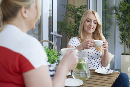 gente sentada: El buen tiempo para tomar un café fuera