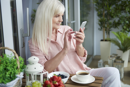 one senior woman only: Checking recent news on the phone