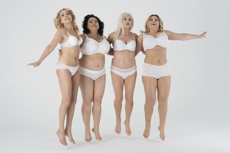 Glückliche Frauen, die im Studio springen