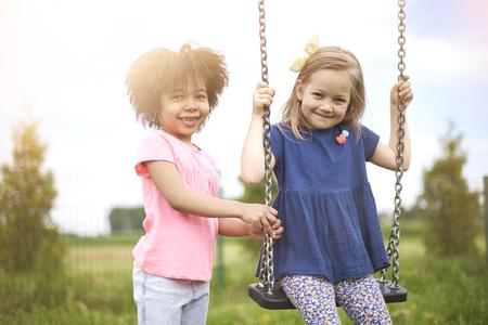 niño empujando: Los mejores amigos en el patio de recreo
