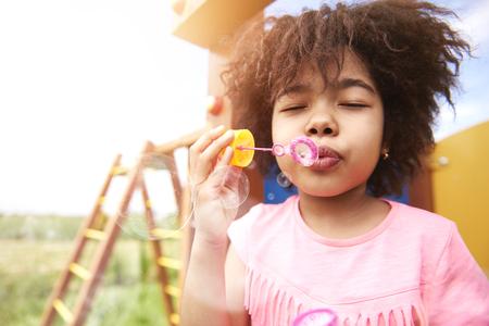 niños riendose: burbuja de jabón en el parque infantil Foto de archivo