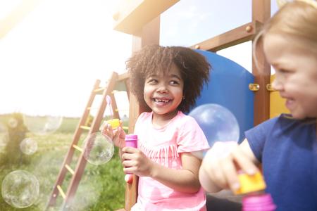 niños felices: Soplando burbujas de jabón con el mejor amigo