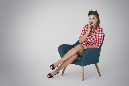 Beautiful pin up girl in the armchair