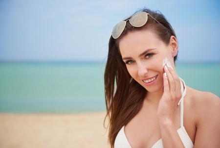 suntan lotion: Applying suntan lotion on the face