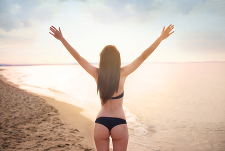 rear view: Rear view of woman by the sea Stock Photo