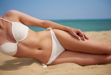 lower body: Nicely tanned woman on the beach Stock Photo
