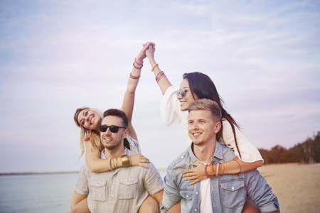 carrying: Boys carrying their attractive girlfriends Stock Photo