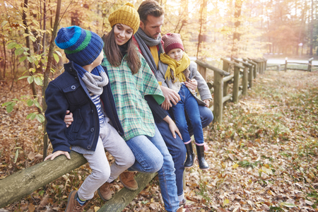leaning by barrier: Family time in the forest