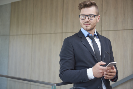 mobilephone: Handsome and pensive businessman with mobilephone Stock Photo