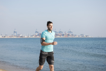 Handsome man running by the sea
