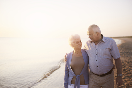 happy seniors: Talking and walking on the beach