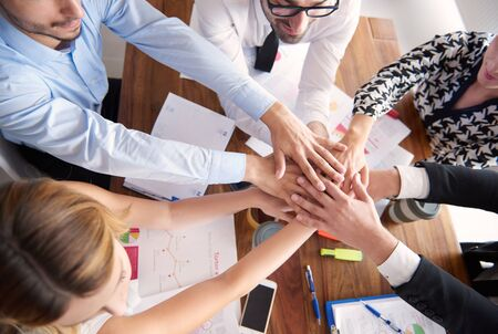 huddling: Stack of human hands above the table Stock Photo