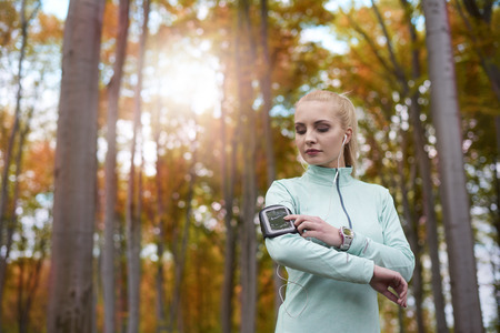 Woman jogging in the forest with good music Stock Photo