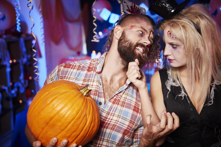 dressing up costume: Scary couple with big pumpkin Stock Photo