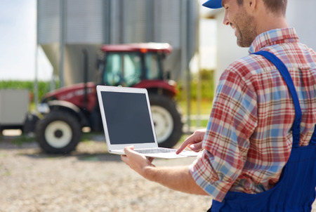 Farmer usando la computadora portátil en la granja Foto de archivo - 63188591