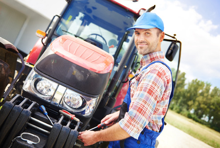 Farmer repairing his big tractor Stock Photo