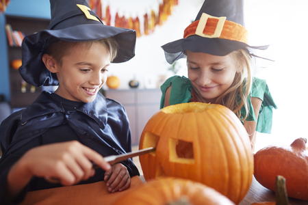 sibling: Elementary age sibling drilling in pumpkin Stock Photo