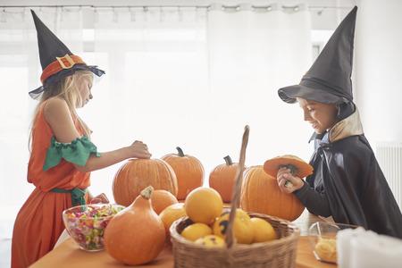 Little siblings to work on Halloween pumpkins Stock Photo