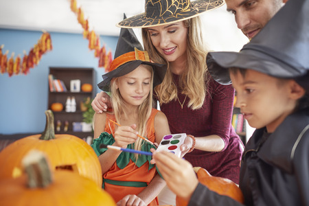 Kids with parents painting Halloween pumpkins