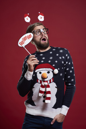 red cardigan: Man holding a Christmas mask Stock Photo