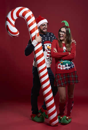 Man embracing candy cane and his girlfriend Stock Photo