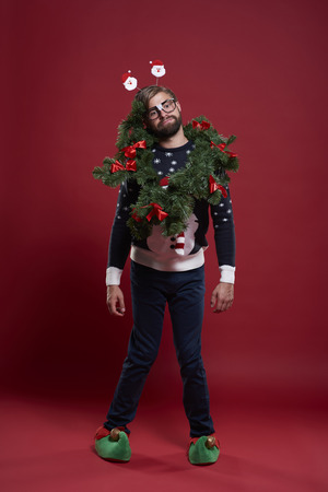 Man wearing christmas clothes and a garland