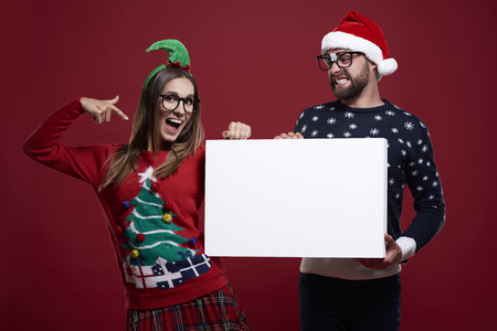 unfashionable: Pointing on placard in christmas clothes