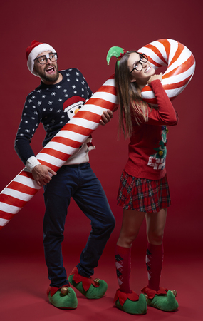 suffocate: Couple carrying heavy candy cane Stock Photo