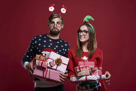 Happy couple with gifts on red background