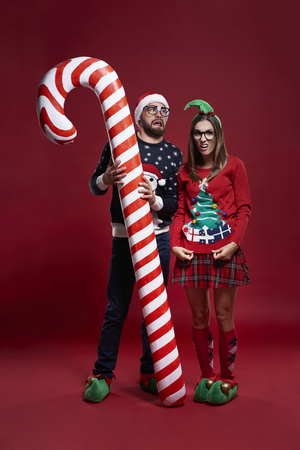 unfashionable: Weird Christmas couple with candy cane Stock Photo
