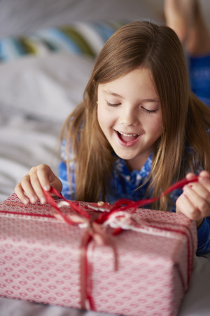 exciting: Exciting girl opening Christmas present