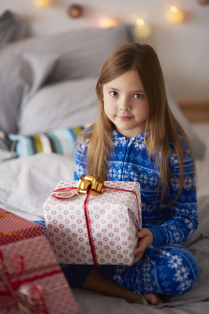 Beautiful girl with Christmas present in the bed Stock Photo