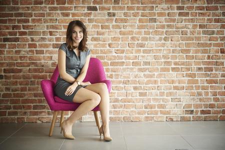 mujer sentada: Mujer que se sienta cómodamente en la silla