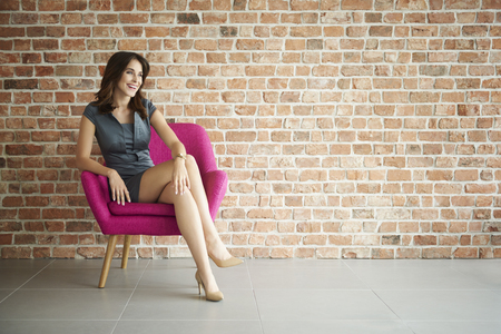 Attractive and cheerful woman in the armchair