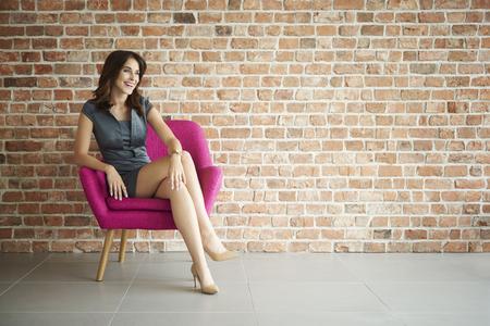 mujeres morenas: Mujer atractiva y alegre en el sillón Foto de archivo