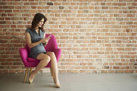 women sitting: Browsing phone on pink armchair Stock Photo