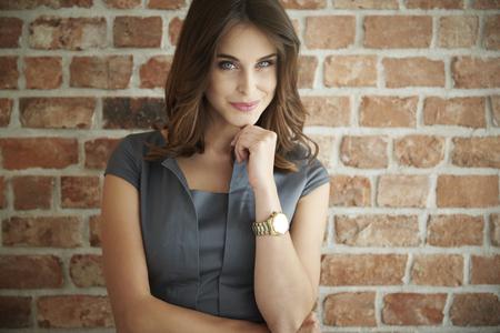 Mooie bedrijfsvrouw die zich vooraan de muur bevindt